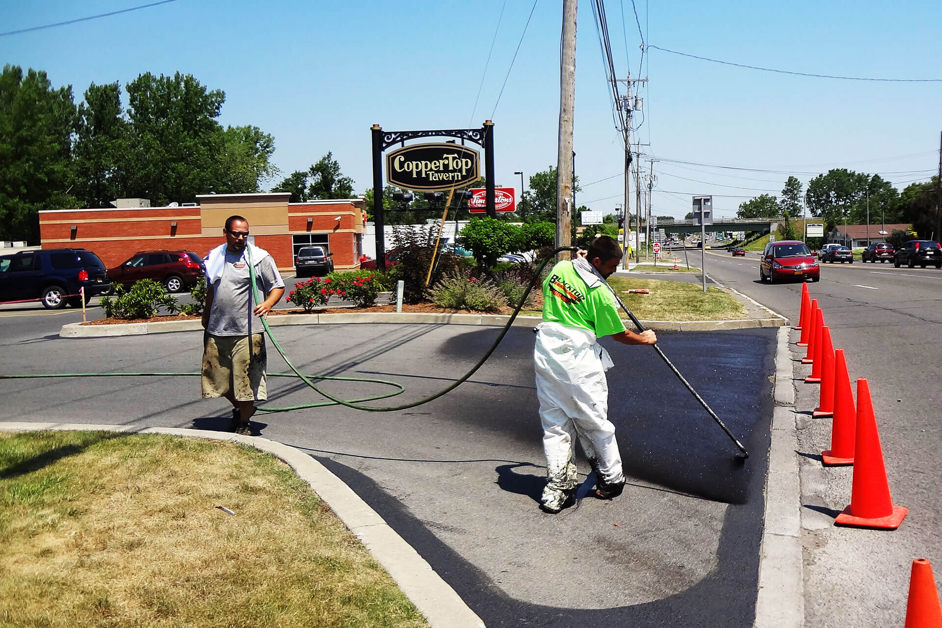 Workers sealing pavement